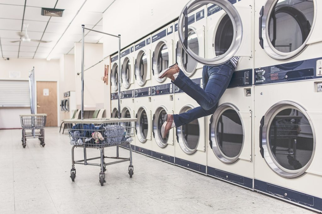 woman struggling to do laundry at the laundromat